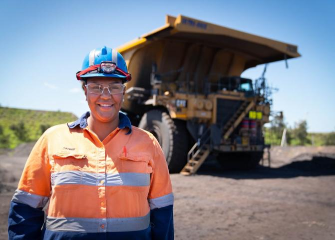 Woman in high vis uniform and mining tractor