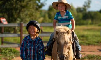 Children riding horse in outback